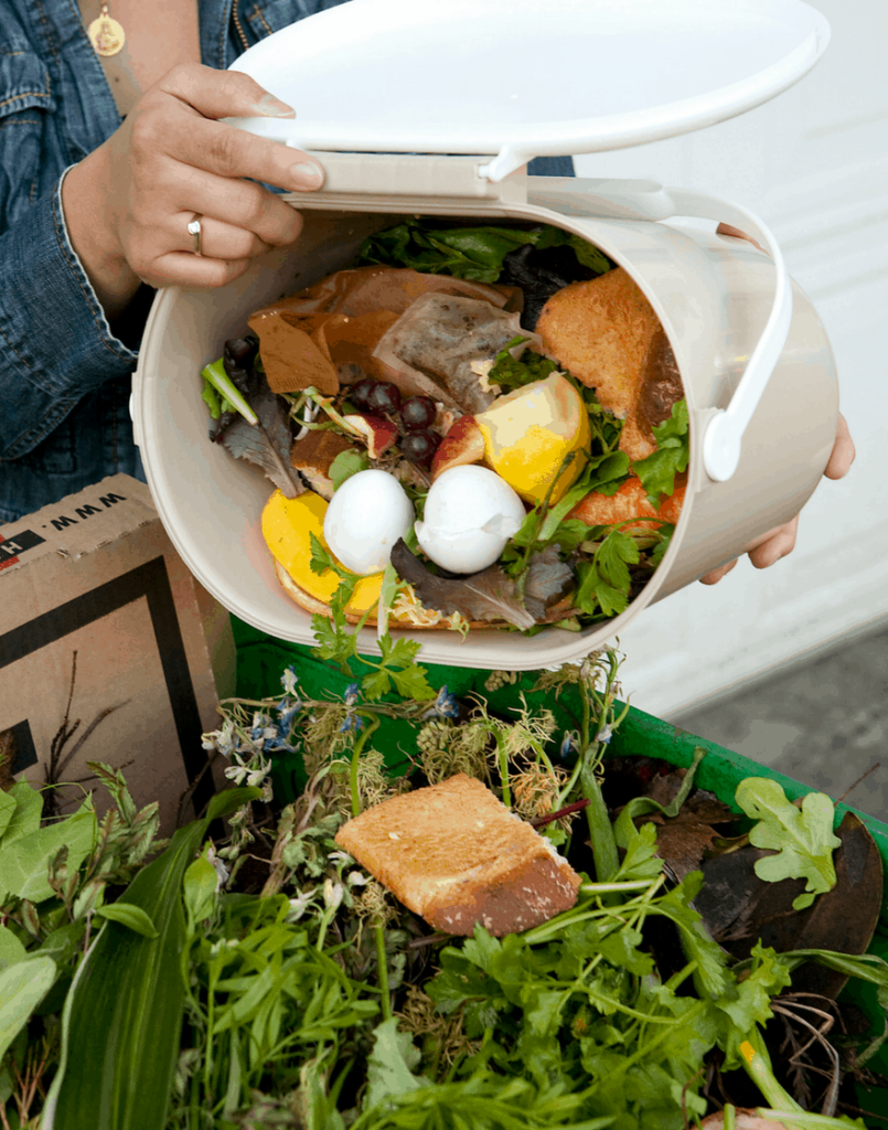 pouring food scraps into compost bin