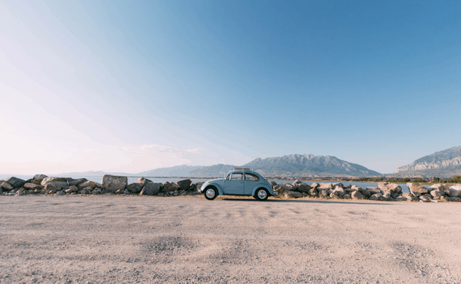 volkswagen bug parked at the side of the road with a view