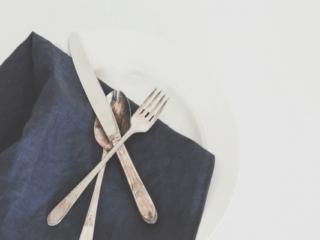 set of silverware on a dark blue napkin