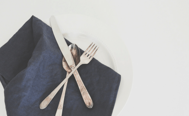 set of silverware on a dark blue napkin